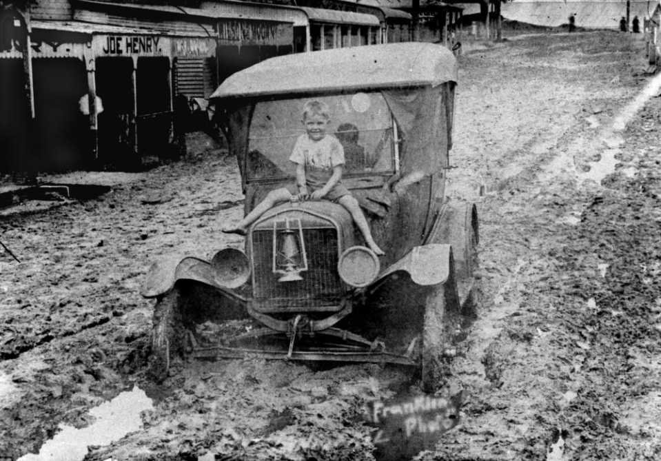 Date: Circa 1917-1927 Location: Rankin Street, Innisfail,  Who: Boy sitting on a car during the flood